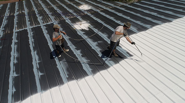 Roofers applying butyl elastomeric coating to a metal roof