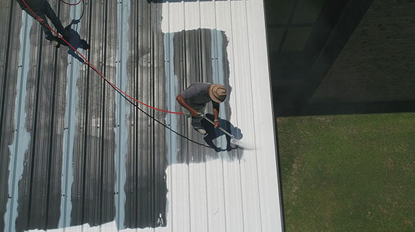 Roofers spraying butyl elastomeric coating on a commercial metal roof