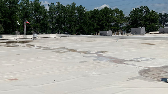 Commercial flat roof inspection of water pooling and penetration damages