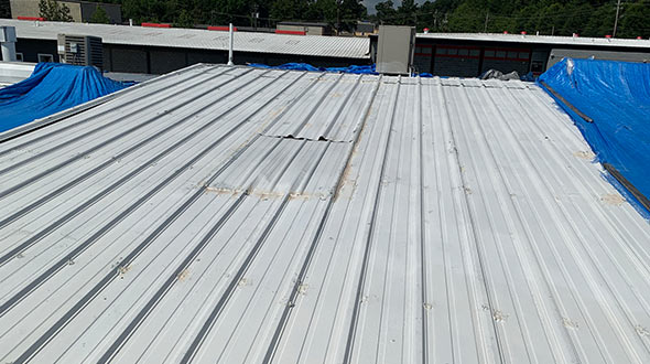 Commercial metal roof with corrosion and damaged seals