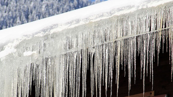 Ice dam freezing water damaging a commercial roof