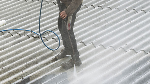 Commercial roof power washing before protective coating application