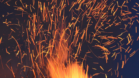Wildfire embers ignite combustible material in gutters and roof